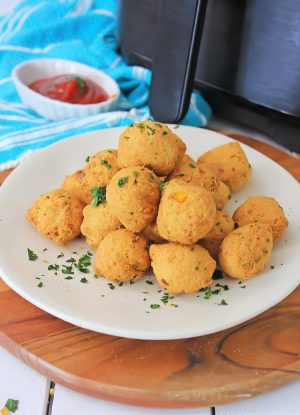 plate of fresh hush puppies and dipping sauce in front of the air fryer