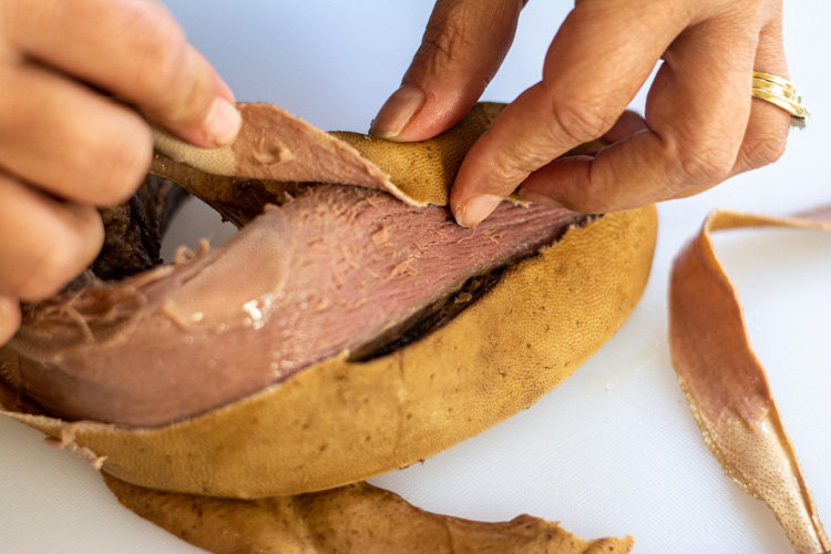 Removing the thick protective skin from the lengua to get to the meat.