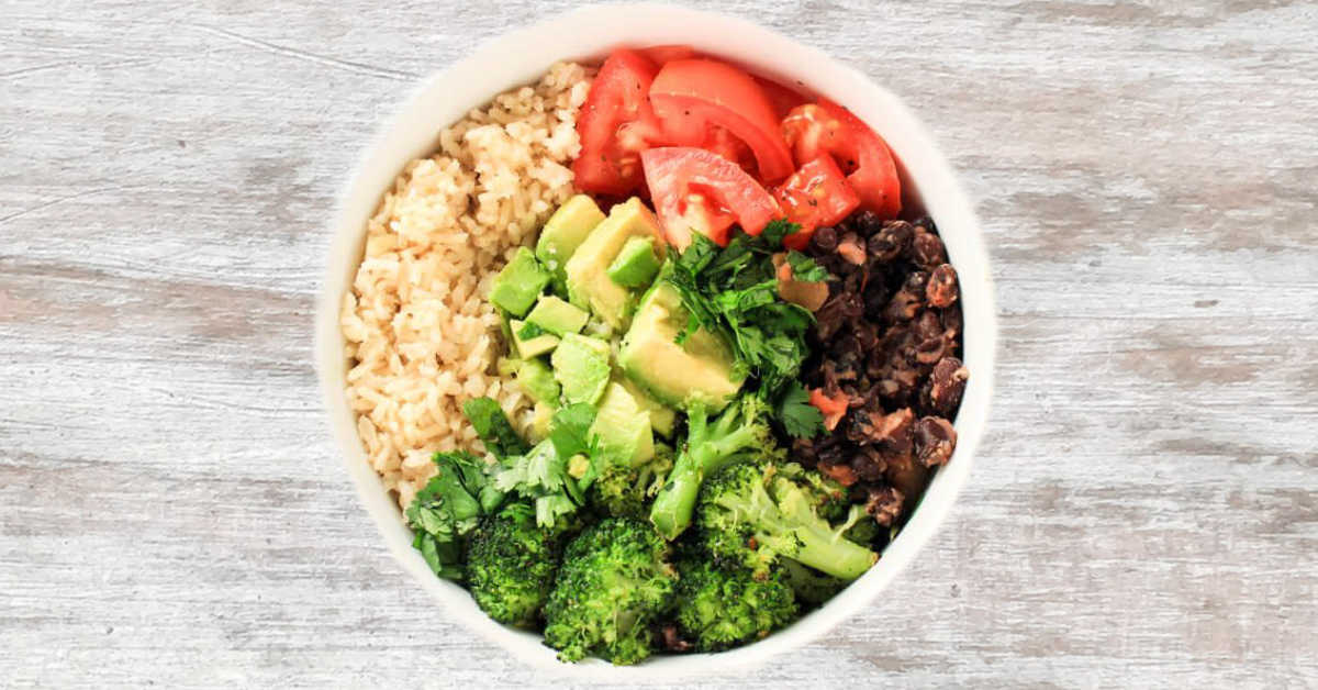 top down view of a vegan buddha bowl filled with fresh veggies and rice