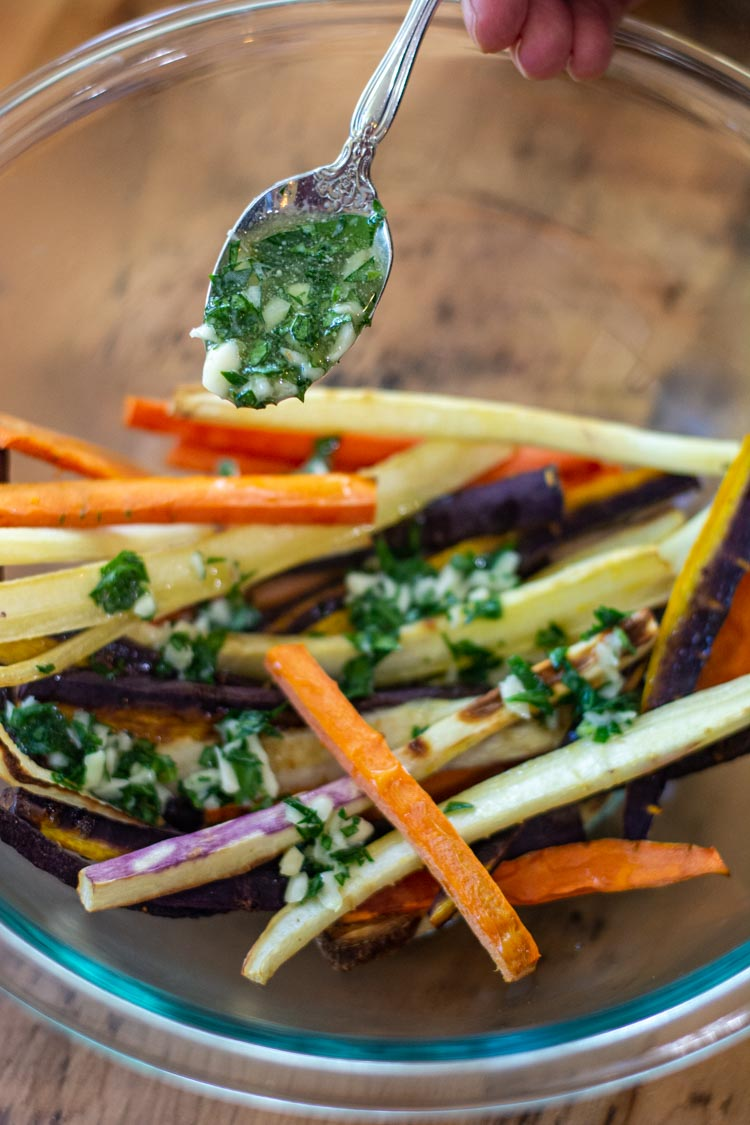 Adding the garlic herb butter with a lot of fresh parsley to the bowl of air fryer carrots.