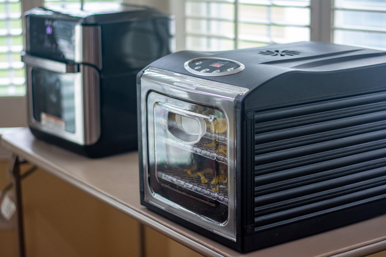 air fryer and dehydrator set up on a foldable table in the dining room