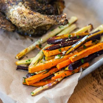 pile of fresh air fryer carrots on a sheet pan with the cooked Cornish hen