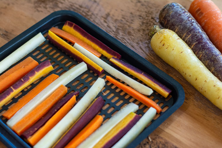 tray with colorful carrot slices and fresh whole carrots in the background