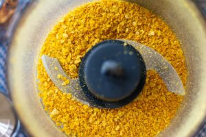 Top down view of food processor after grinding the dried lemon peels into powder