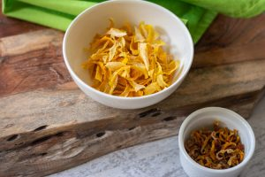 two bowls of dried lemon peels. One is bright yellow from the dehydrator and one is darker from the higher temperature in the oven