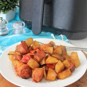 large plate of kielbasa and potatoes in front of the air fryer
