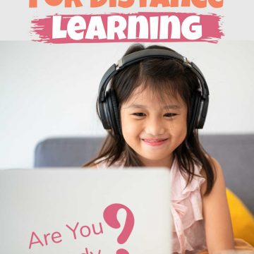 little girl with headphones in class on her laptop
