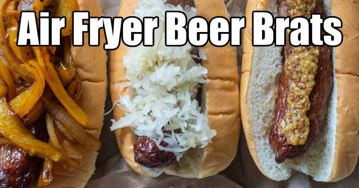 three beer brats in buns with onions and peppers, sauerkraut, and whole grain mustard