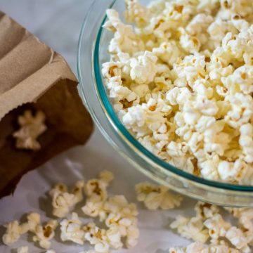 bowl of popcorn and brown lunch bag with open with popped kernels on the table