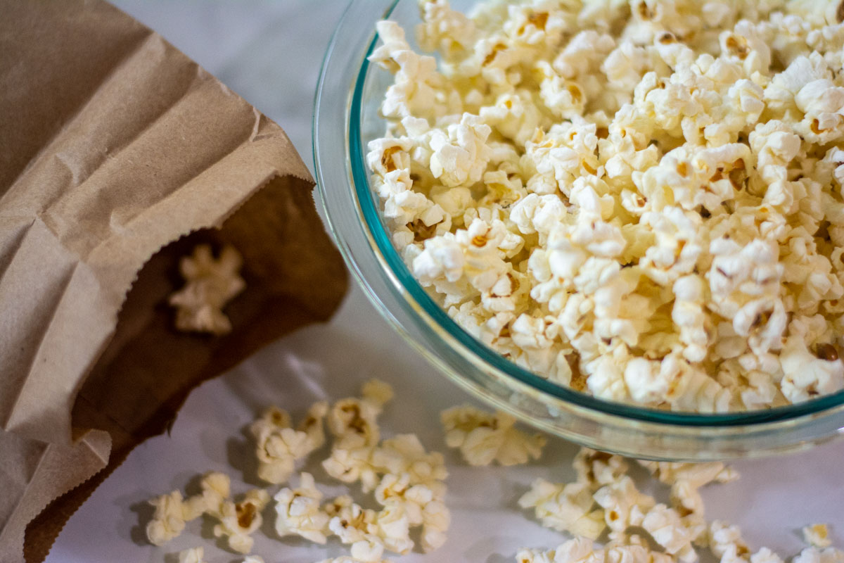 bowl of popcorn and brown lunch bag with open with popped kernels on the table.