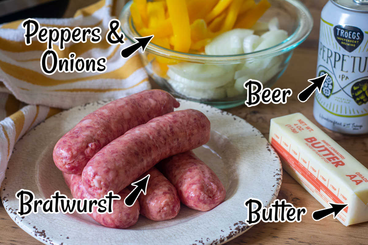 ingredients on a wooden table with labels showing the brats, butter, onions and peppers and the beer