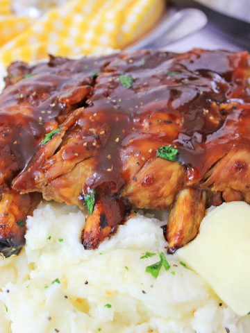 Ribs on top of pile of mashed potatoes with BBQ sauce and the instant pot in the background