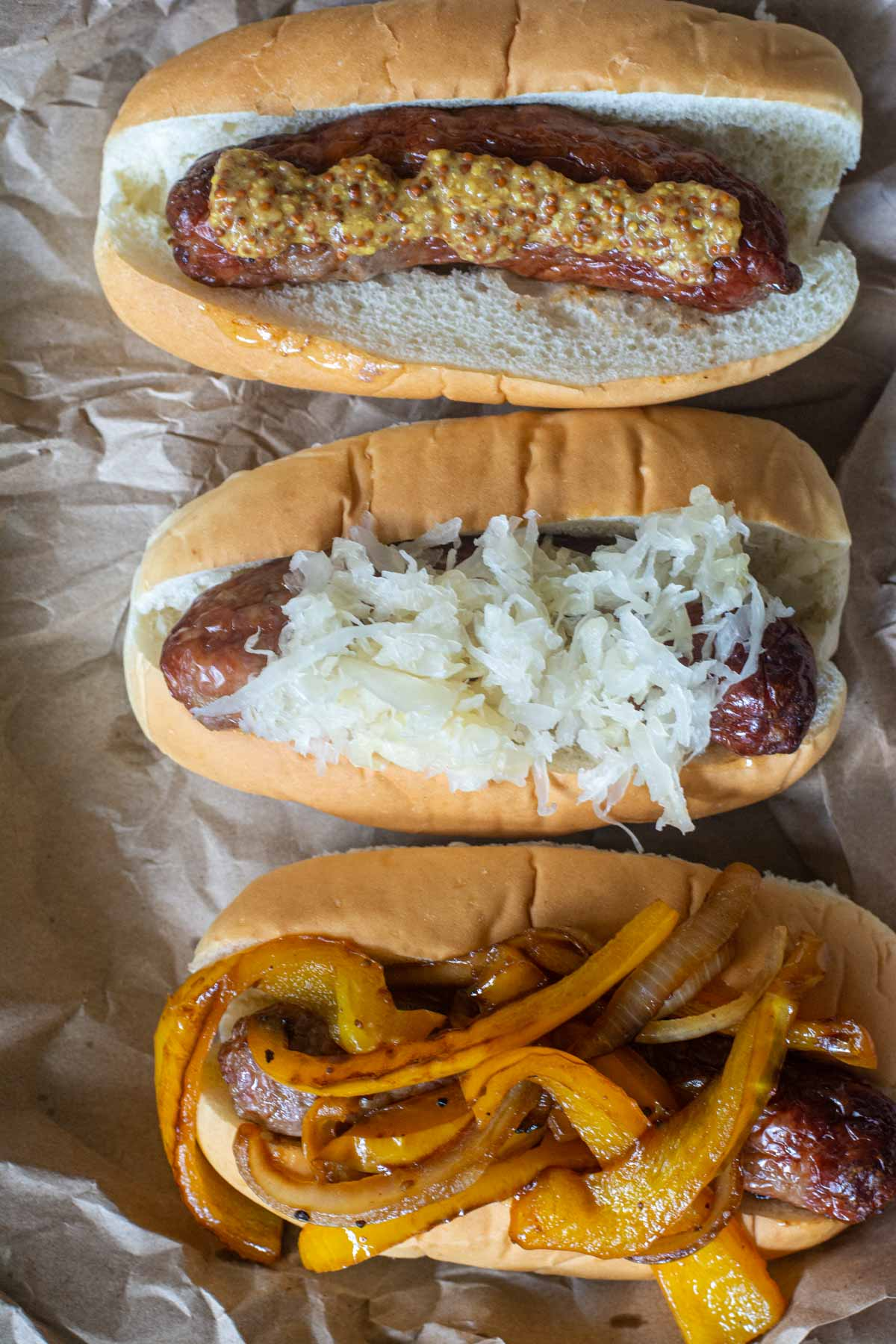 three beear brats in buns with different toppings