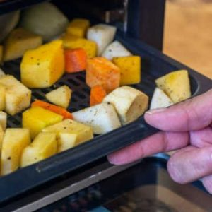 adding a tray of vegetables to the air fryer.