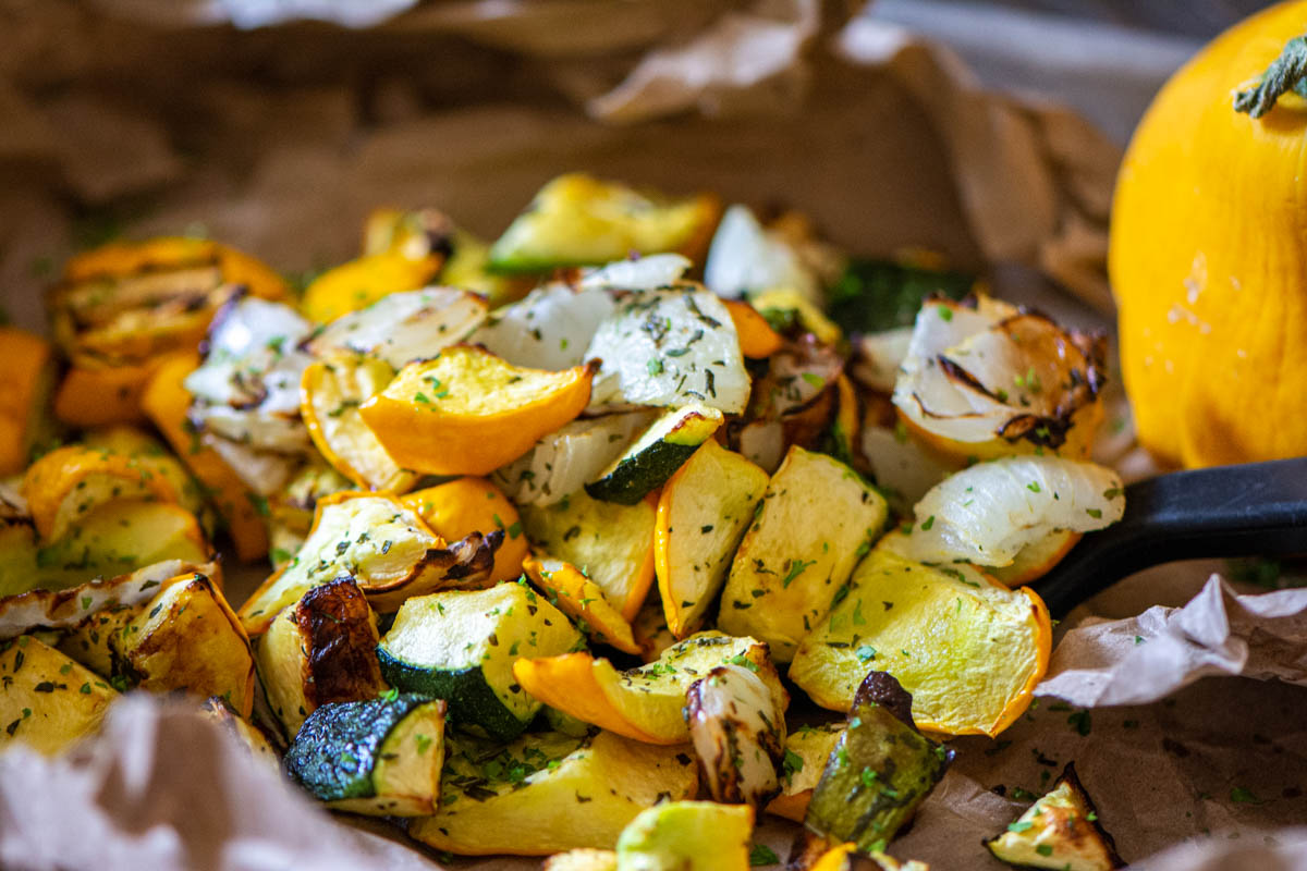 lined sheet pan with cooked squash and a spoon.
