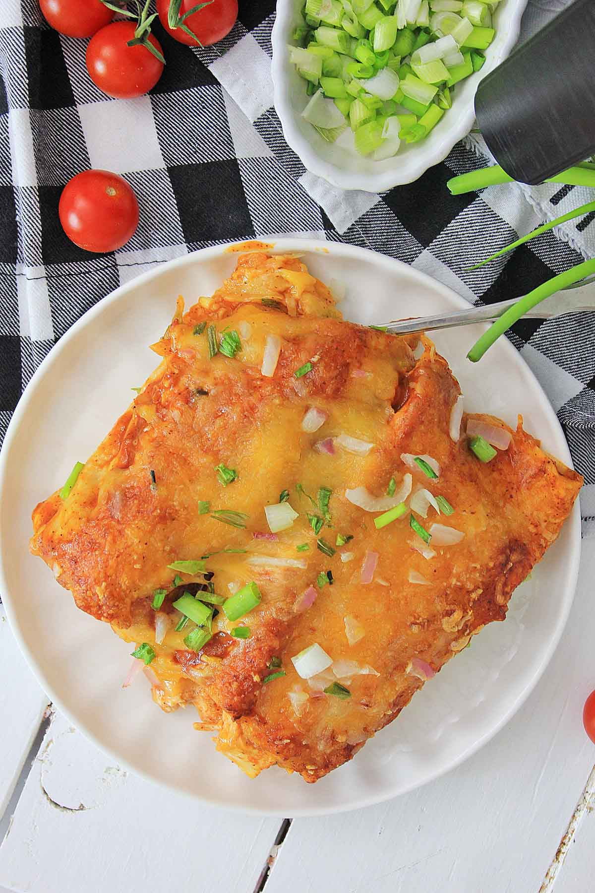 three air fryer enchiladas on a white plate topped with green onions