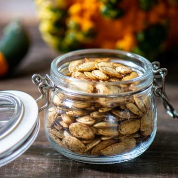 spiced pumpkin seeds made in the air fryer and in front of a decorative gourd.