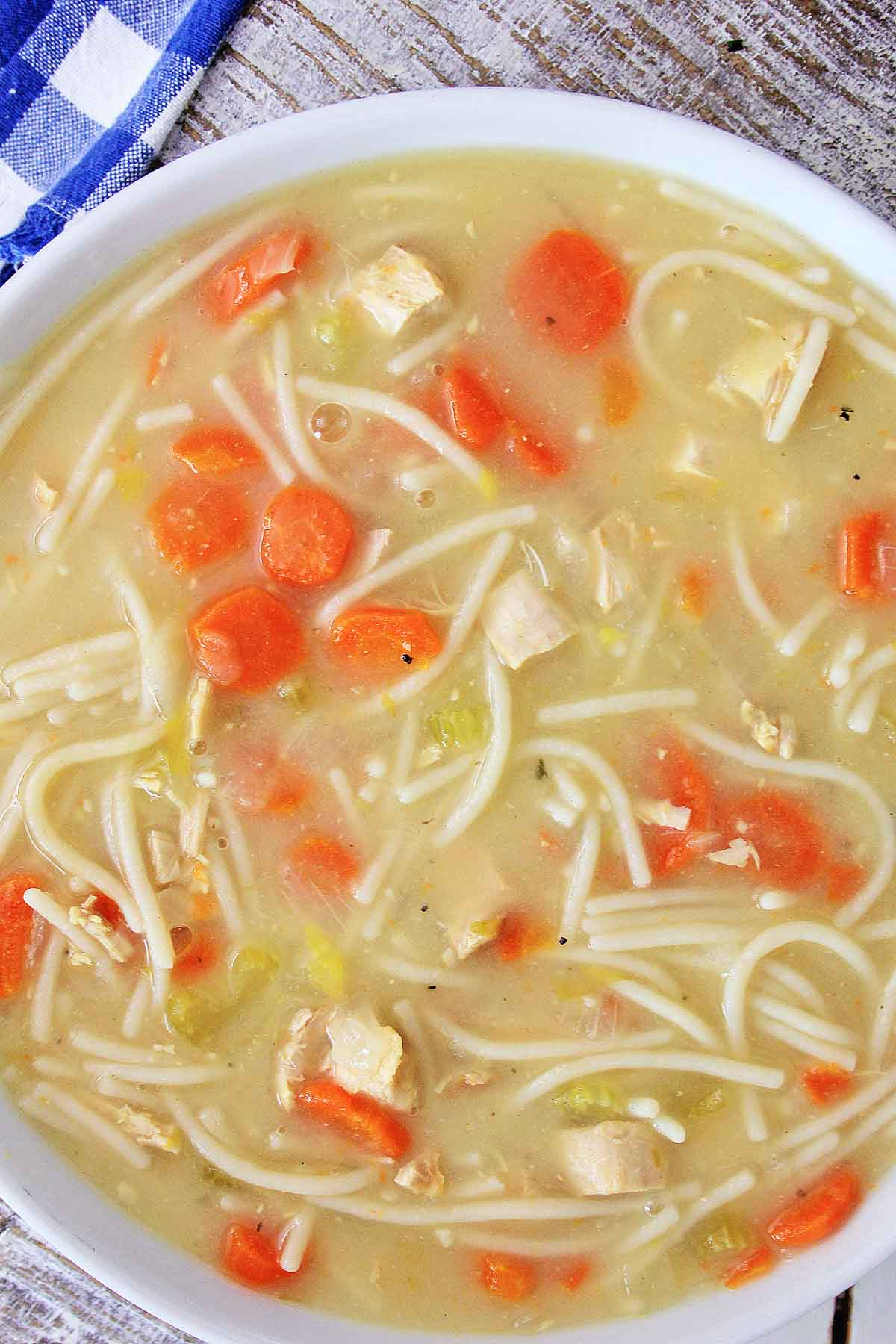 top down view of gluten free chicken noodle soup in a white bowl.