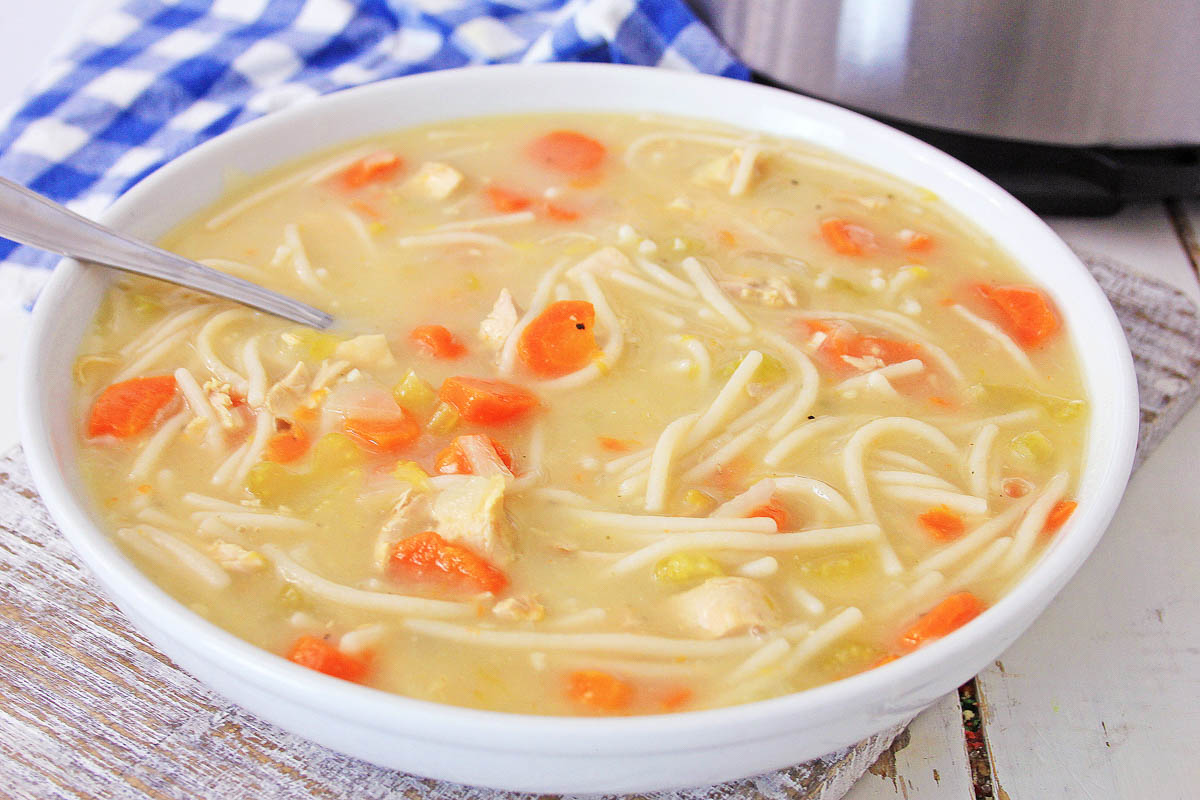 bowl of chicken noodle soup on a white table with a spoon.