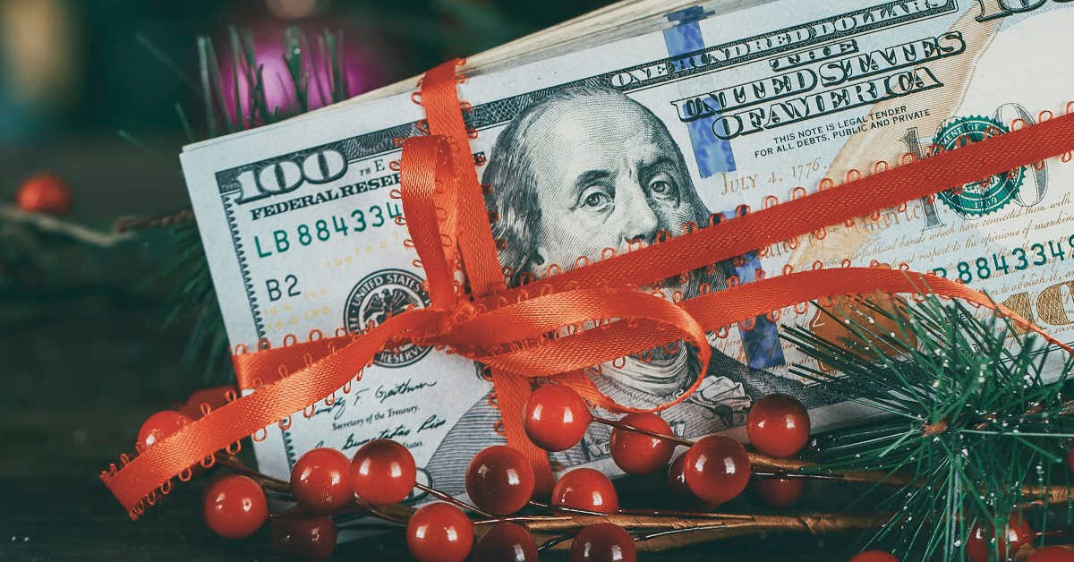 a one hundred dollar bill wrapped in Christmas Ribbon