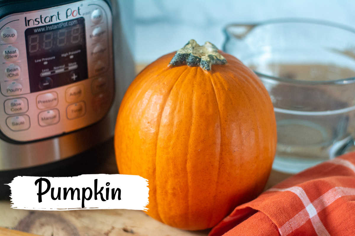 a pumpkin, the Instant Pot and a cup of water on a cutting board.
