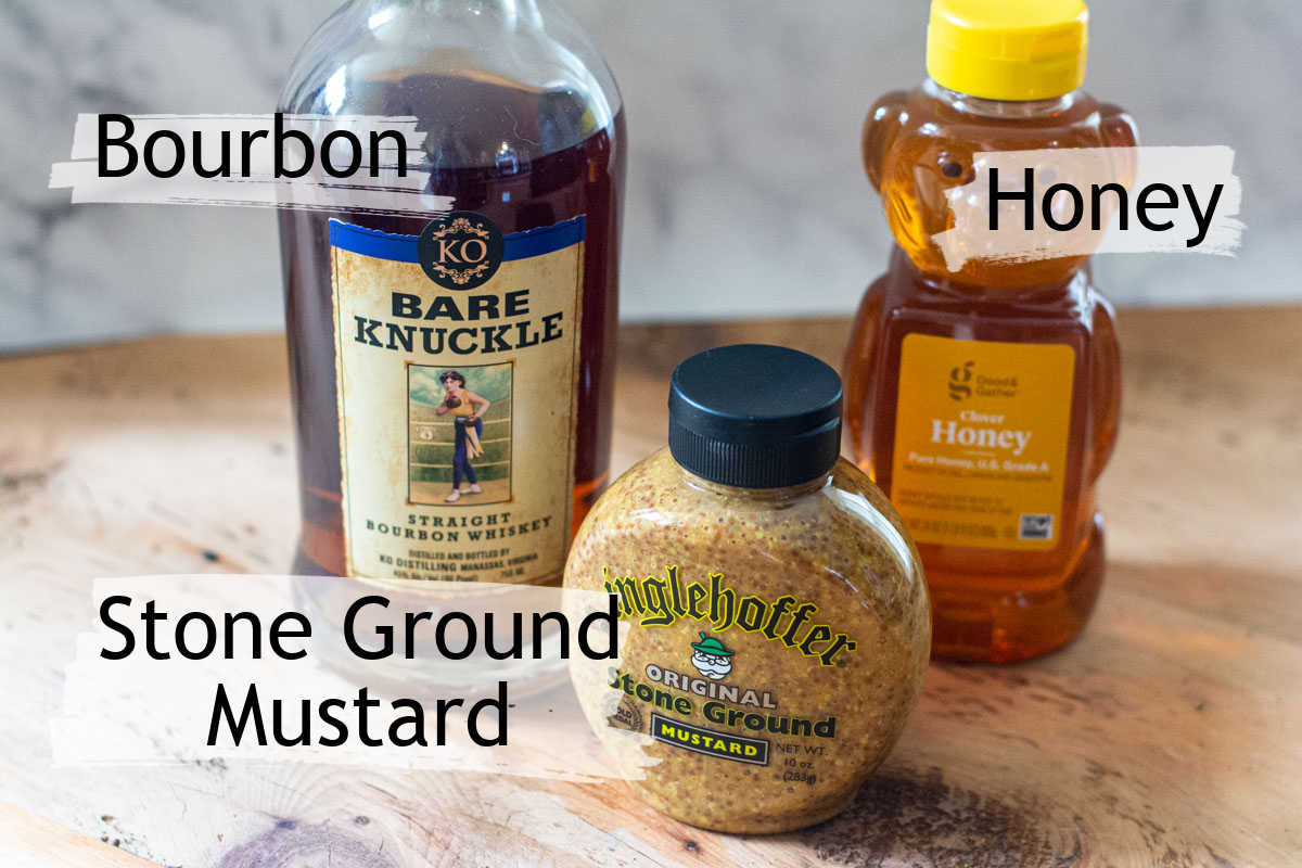 bourbon, homey and stone ground mustard on a table with labels.