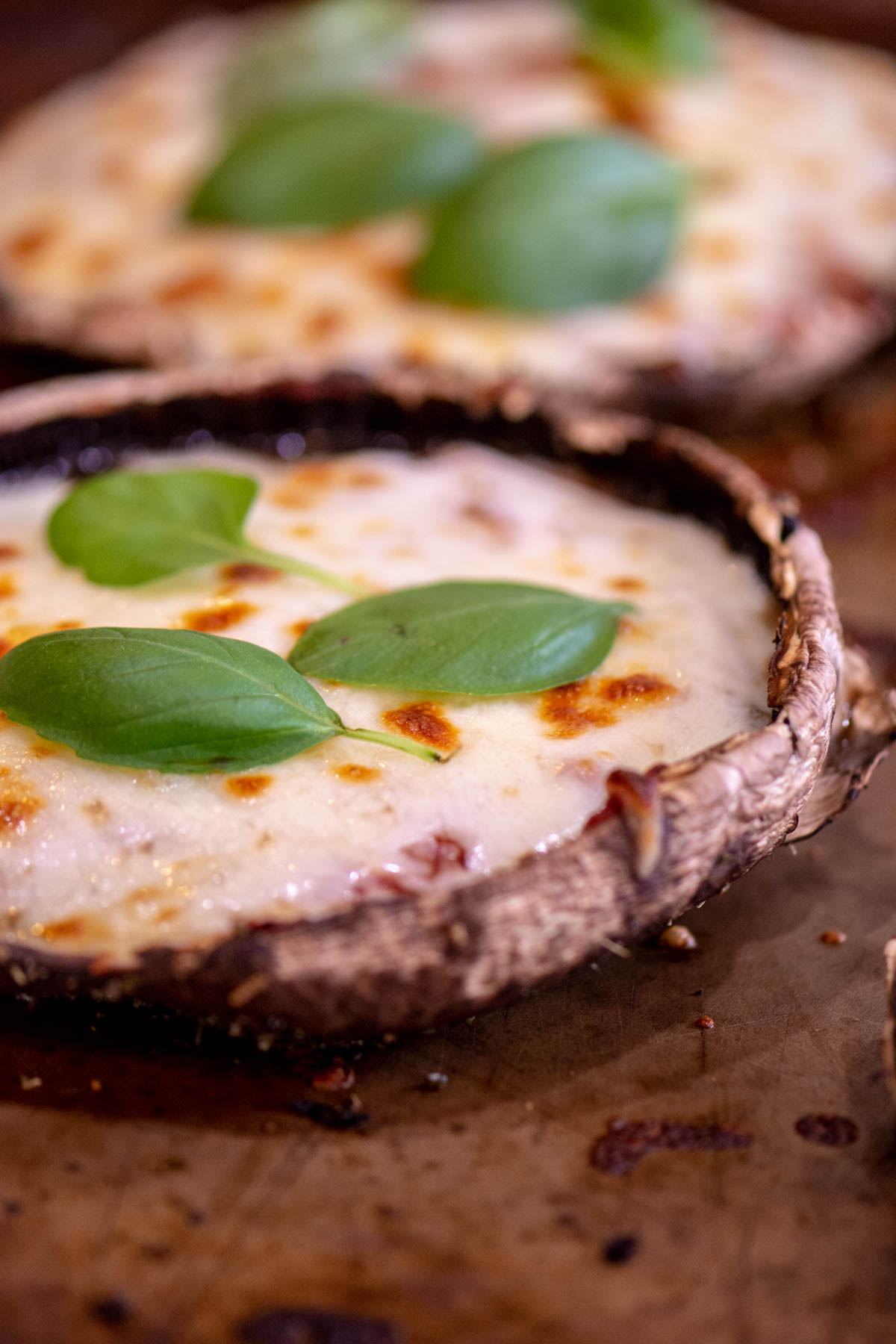 Fresh Basil and Mozzarella on top of the baked Portobello Mushroom on a sheet pan.