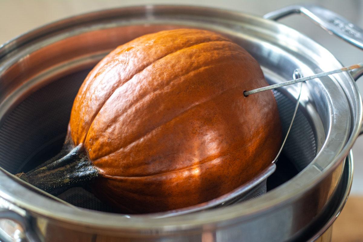 pumpkin in a steamer basket with a skewer inserted.