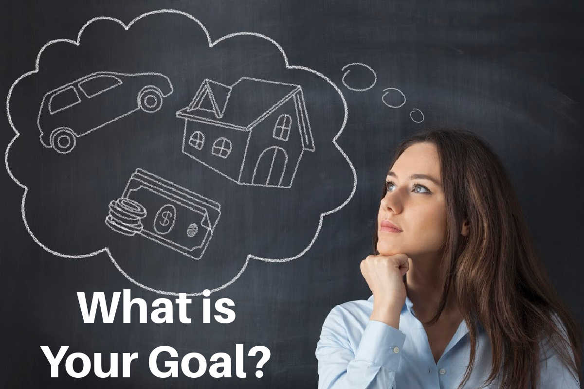 woman in front of a chalkboard and dreaming about a house, a car and more money.