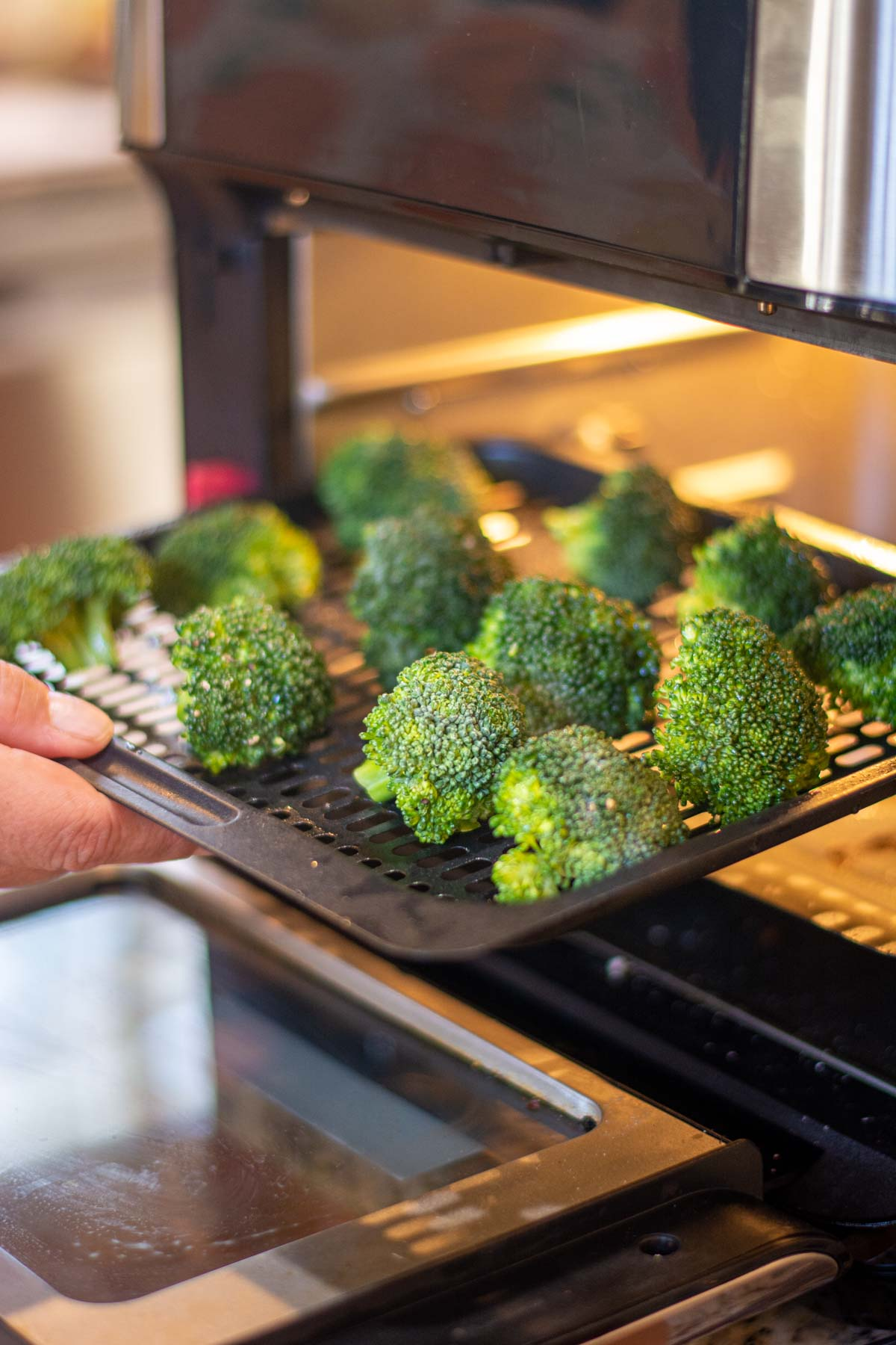 adding the broccoli to the air fryer.