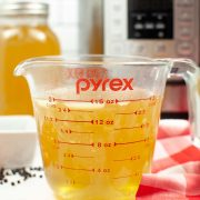 glass measuring cup filled with bone broth and the instant pot in the background.