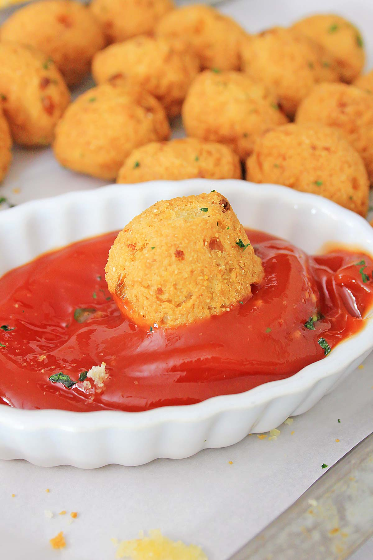 hush puppy dipped in a red sauce with the left over air fryer hush puppies in the background.
