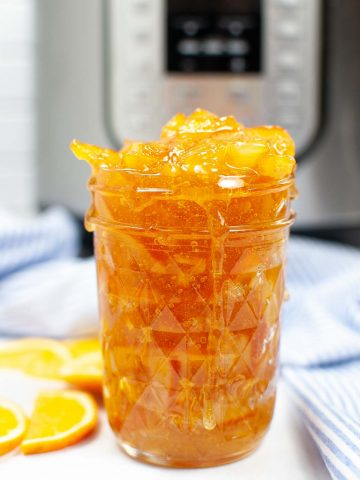 front view of a jar heaping with bright orange marmalade with the instant pot in the background.