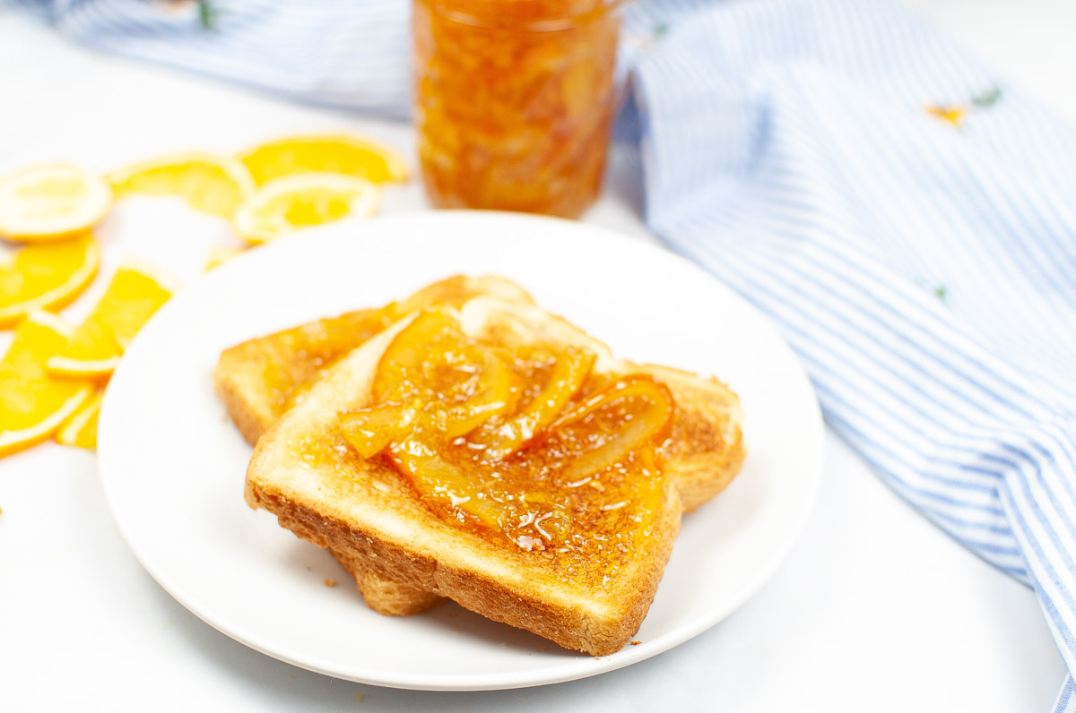 spreading orange jam on toast with slices of fruit in the background.