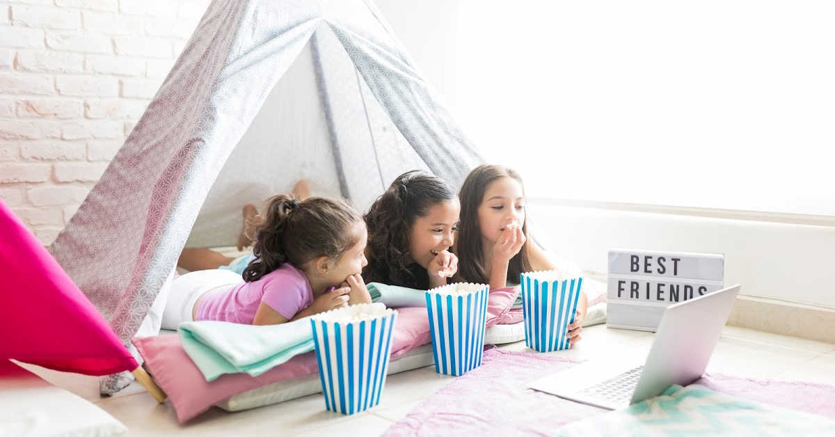 three girls in a homemade fort watching a movie and eating popcorn.