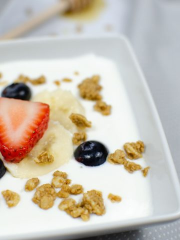 instant pot yogurt in a bowl and topped with berries and granola.