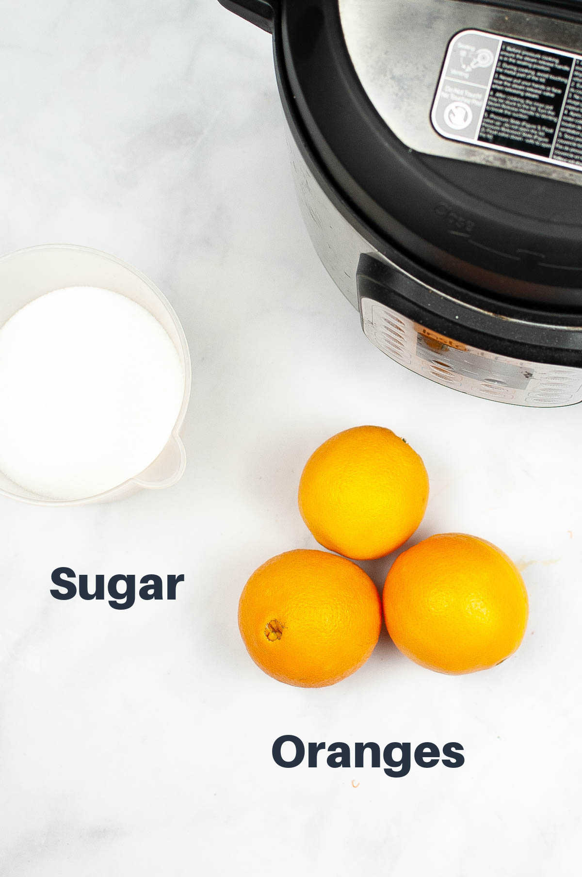 ingredient photo showing oranges and sugar with labels and the instant pot.