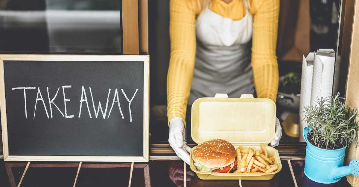 woman opening a container with a restaurant take away meal.