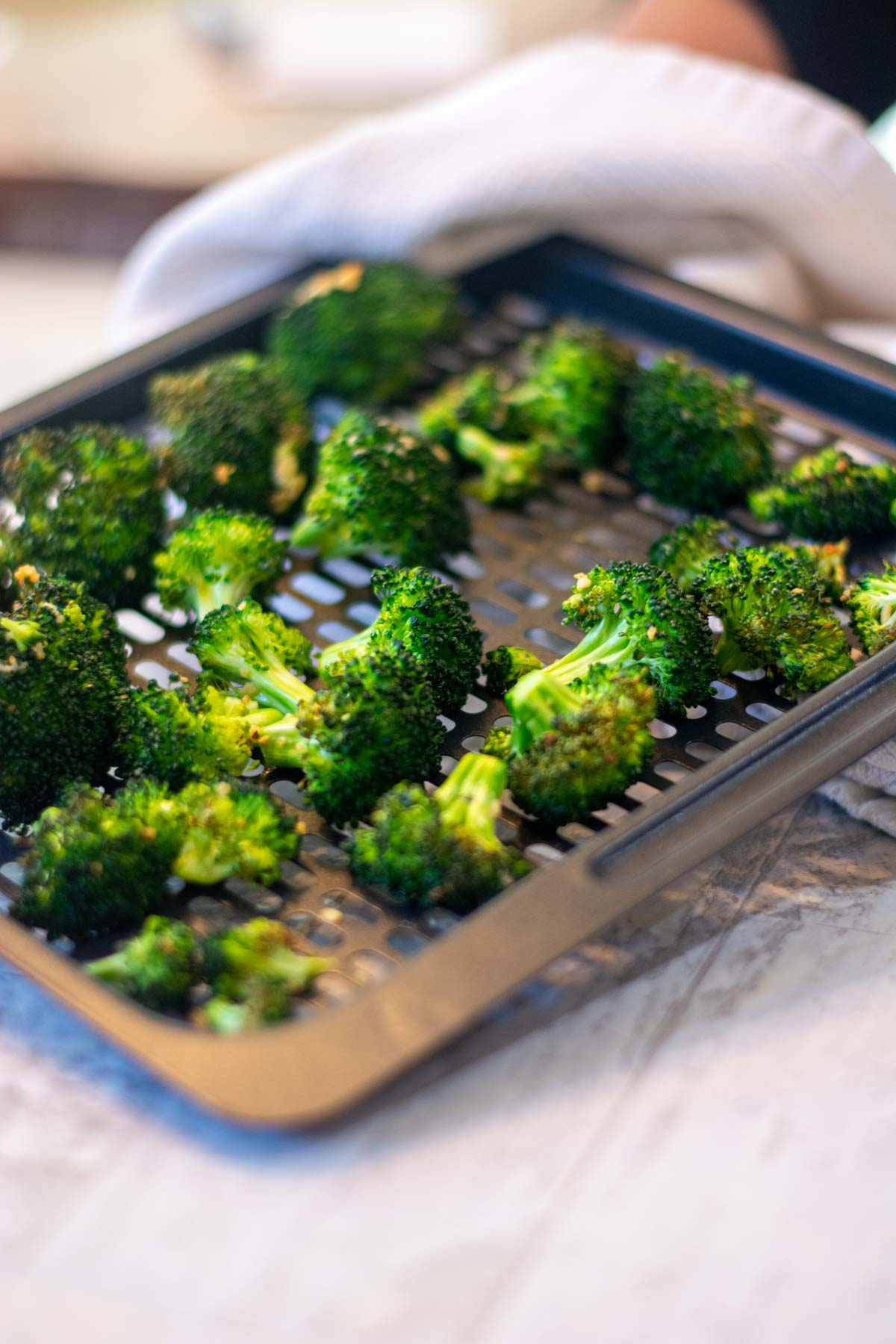 crispy broccoli on an air fryer tray on the counter.