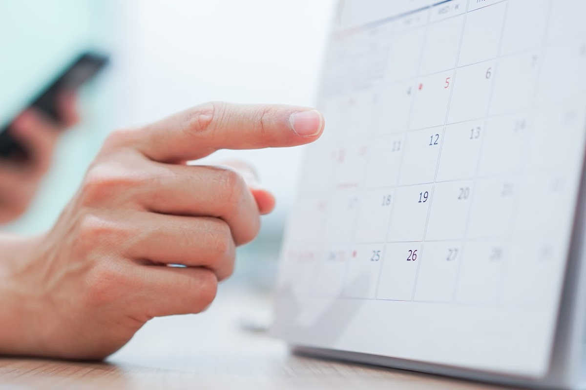 person pointing to a calendar as a reminder to review the budget monthly.