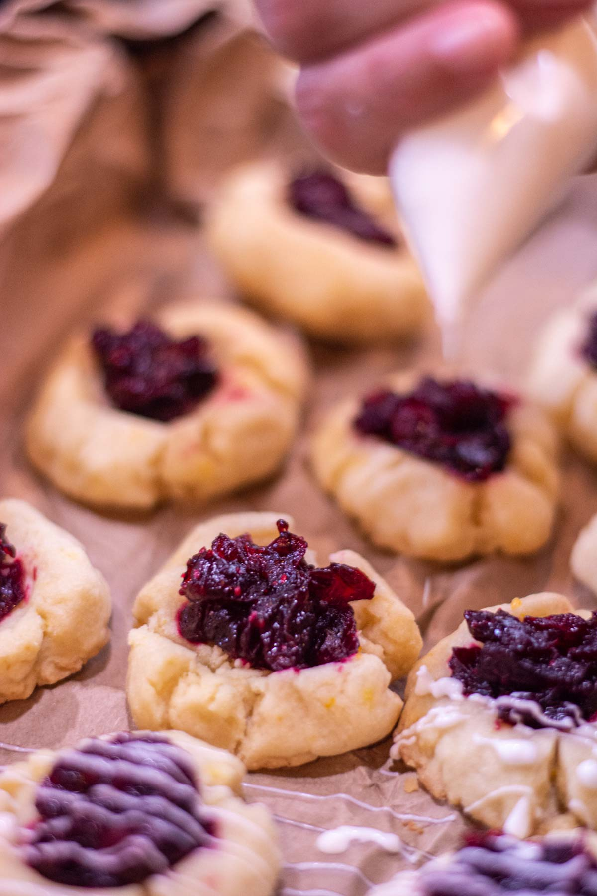 baked cranberry thumbprint cookies with icing being added.