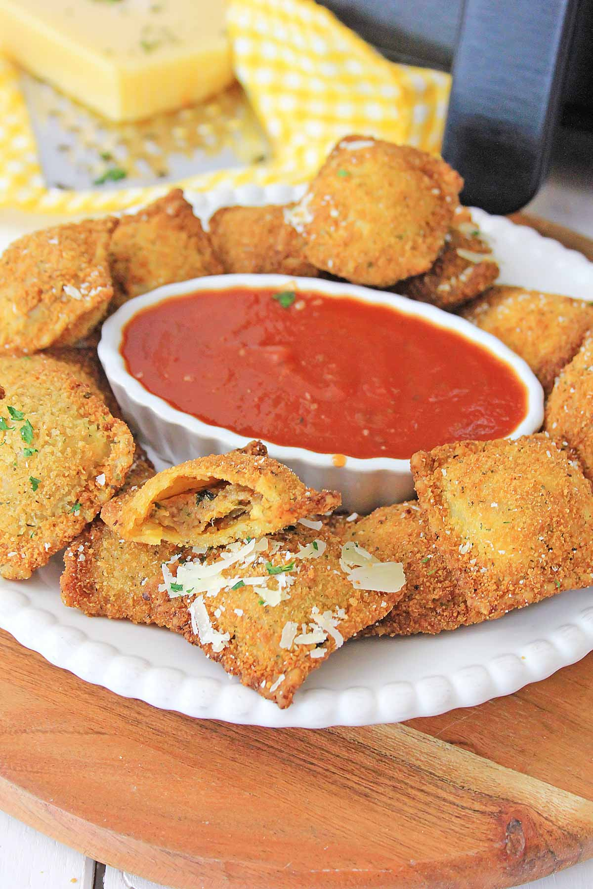plate of air fried ravioli with a red sauce. The air fryer is in the background.