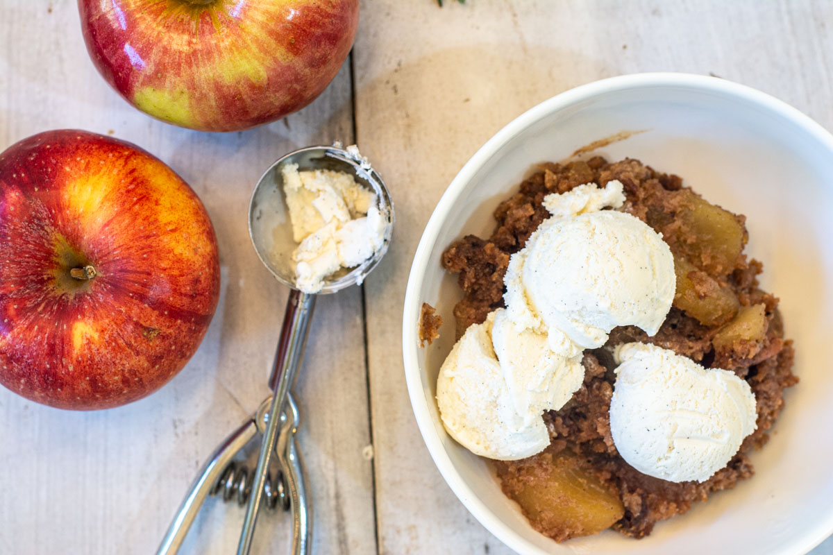 bowl of the apple pie dump cake topped with fresh ice cream and apples.