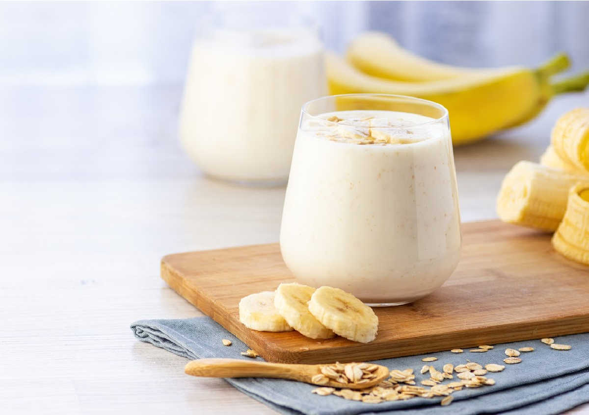 cheap banana smoothie in a glass with slices of fruit and oats.