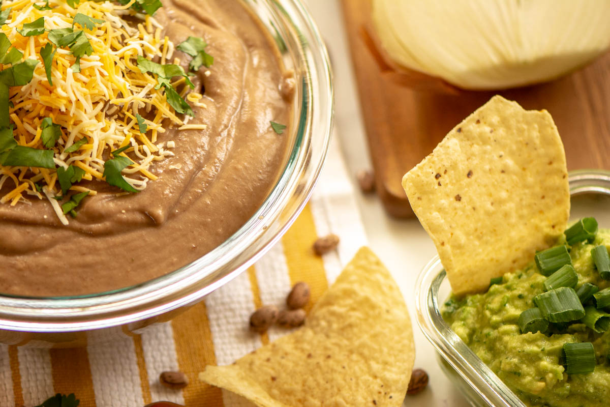 slow cooker refried beans and guacamole with chips.