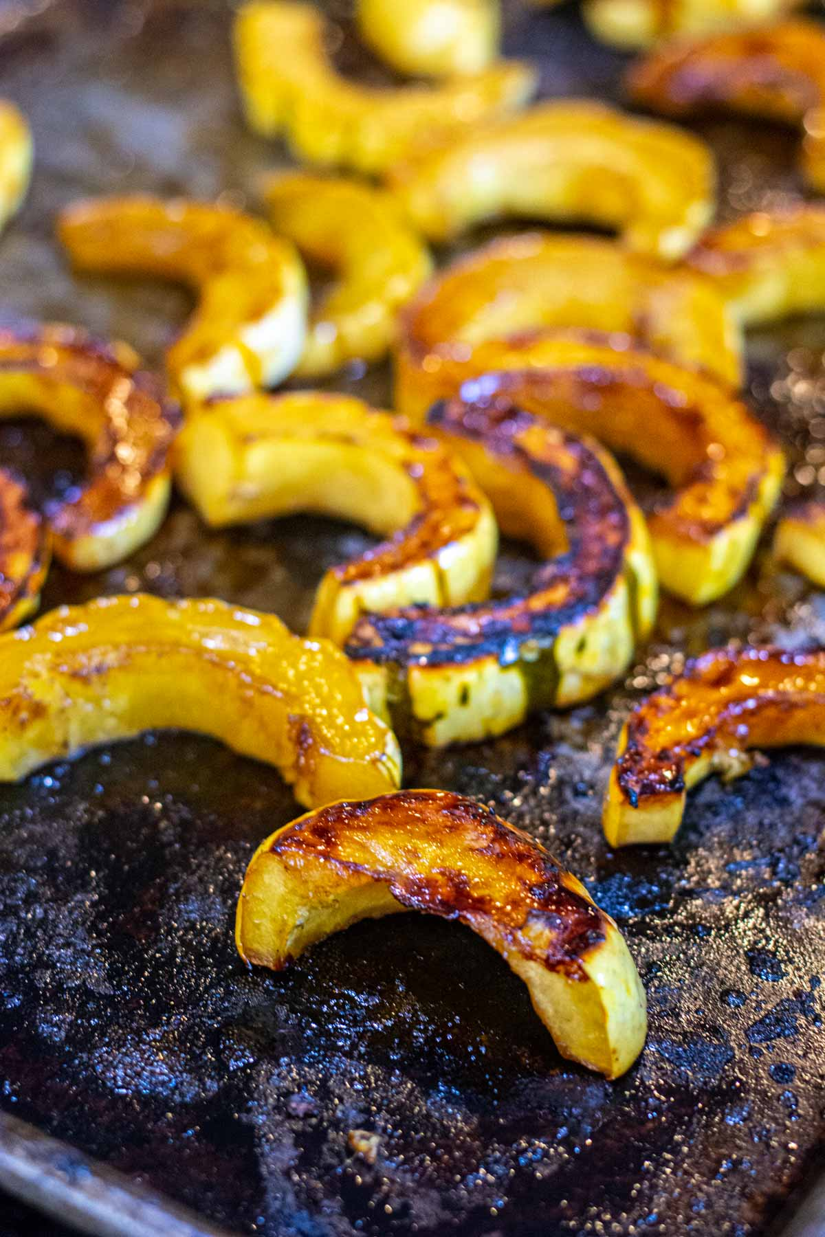 sheet pan with squash rings turned over so you can see the caramelization.