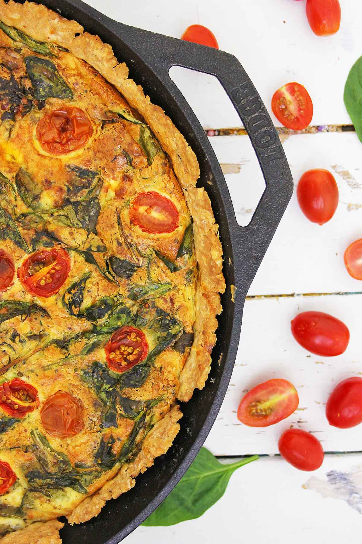 baked tomato and spinach quiche in a cast iron skillet with fresh cherry tomatoes on a white table.