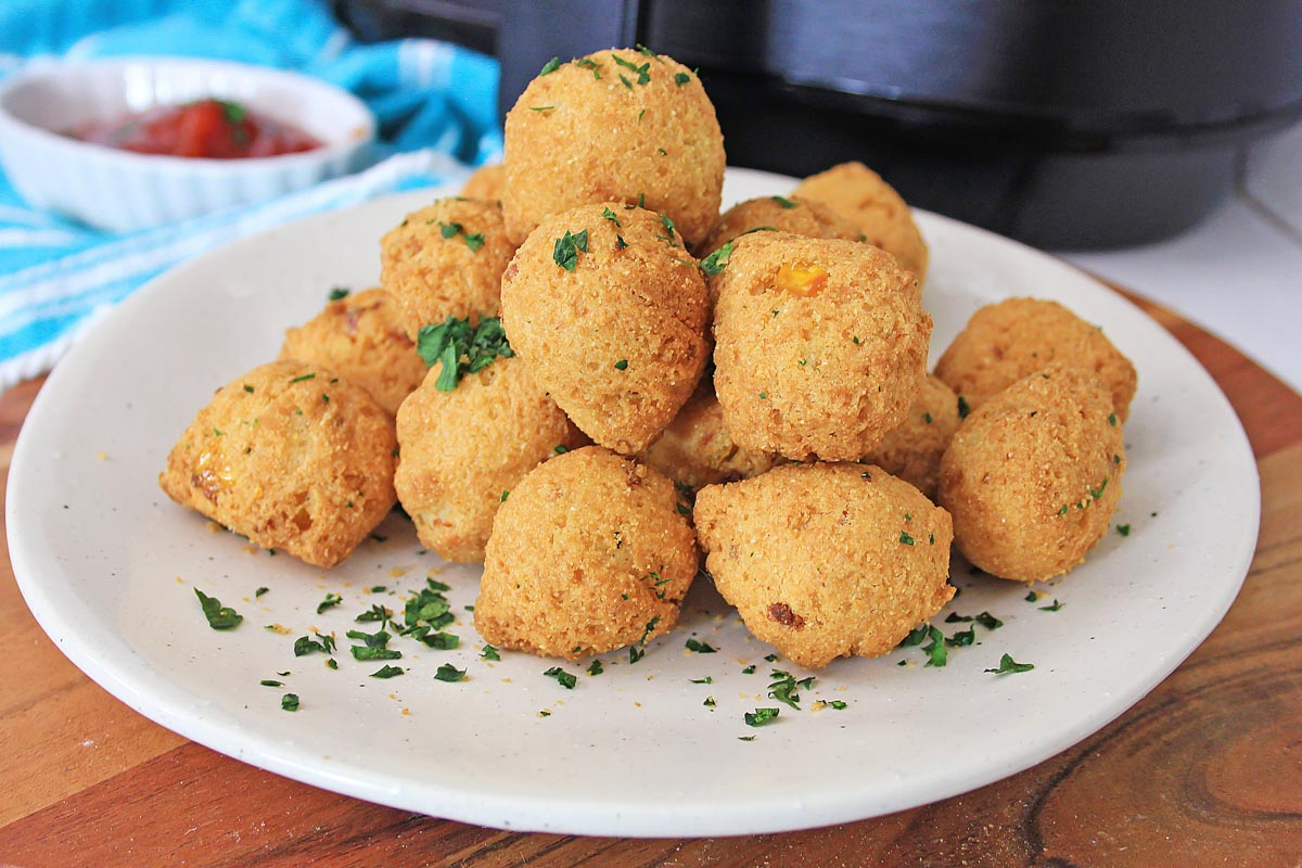 plate of golden brown hush puppies in front of the air fryer and sprinkled with parsley.
