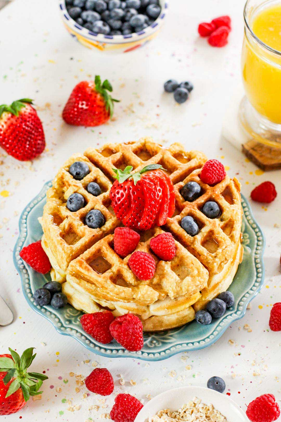 two waffles on a plate with blueberries, strawberries and raspberries on top.