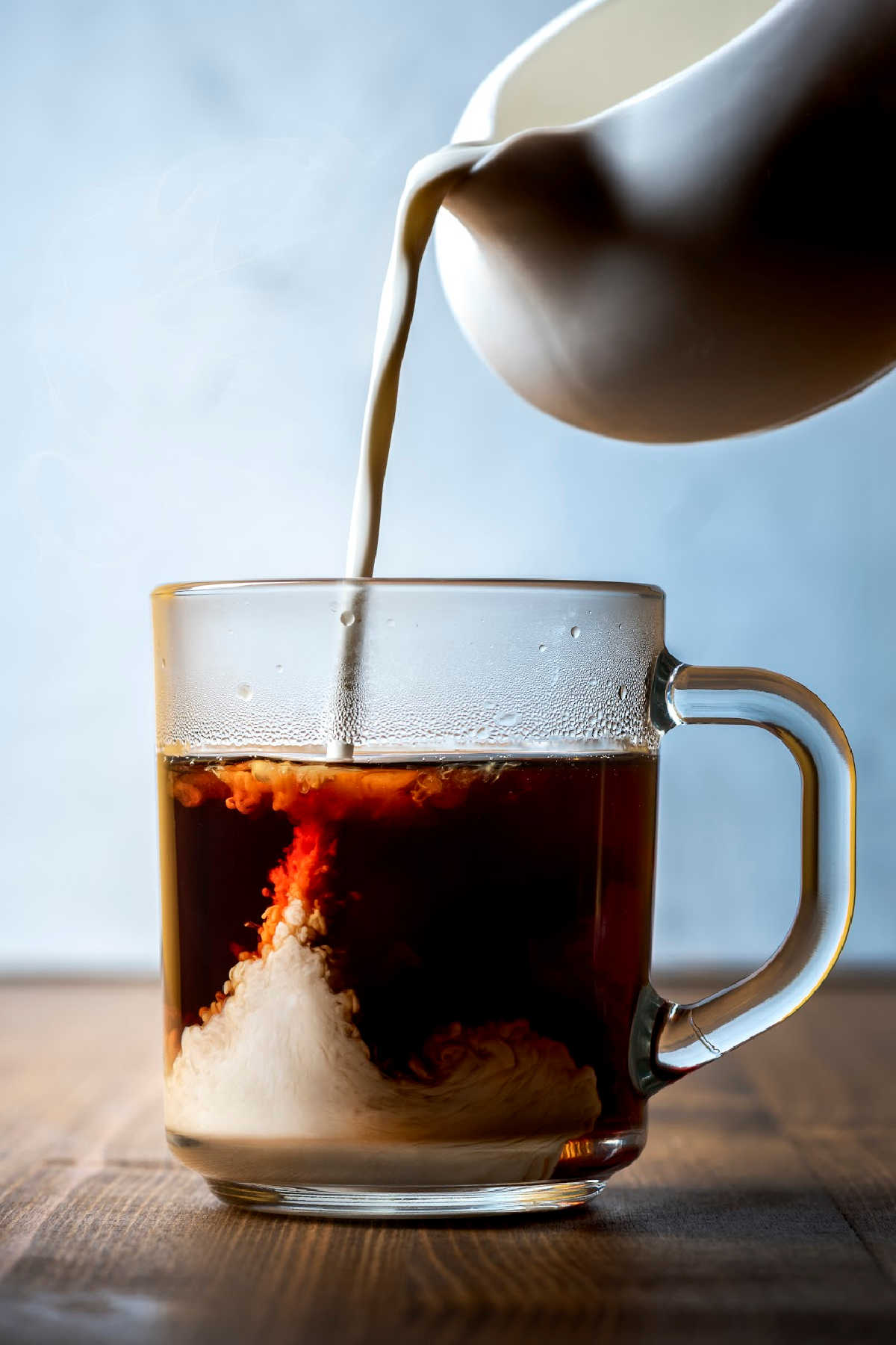 container of homemade coffee creamer pouring into a glass mug with coffee.
